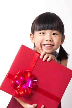 bambini cinesi: Ragazza felice bambino asiatico con confezione regalo rosso per tema natalizio Archivio Fotografico