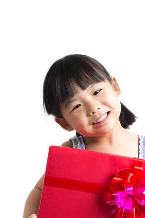 赤いギフト ボックスを持つアジアの子供少女の肖像画をクリスマスのテーマを表します
