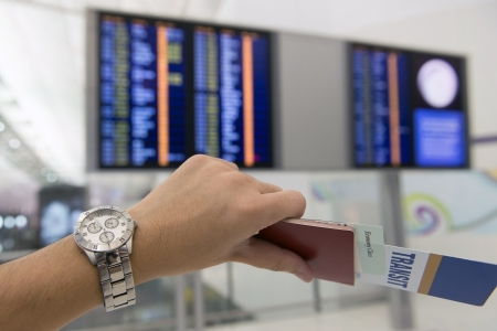 depart: Hand hold a passport, transit pass and ticket checking time to depart