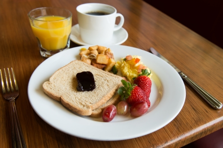 scramble: Typical american hearty breakfast of toast, potato, fruits and juice  Stock Photo