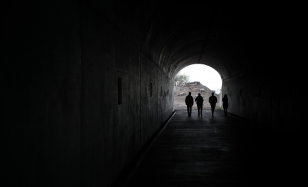 Silhouette of 4 persons walking through a dark tunnel towards the light at the end