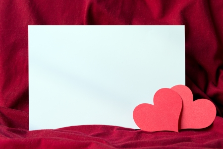 truelove: Blank white paper on red cloth with two red heart shapes Stock Photo