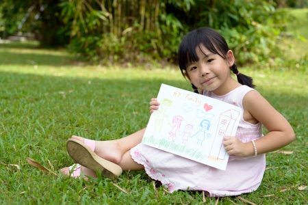 Little child shows drawing of her family member photo