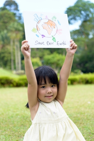environment issues: Little kid showing save our earth drawing in a park