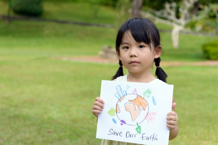 Little kid showing save our earth drawing in a park photo