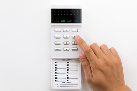 Hand is setting home security alarm system photo