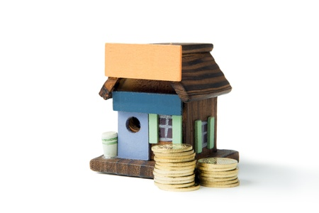 Invest in real estate concept using miniature house and gold coins photo