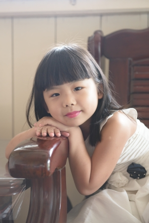 Portrait of little Asian girl in white gown dress photo