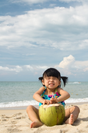 Asian baby girl with coconut fruit on beach photo