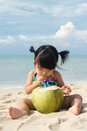 asian baby girl: Asian baby girl drinking coconut fruit on beach