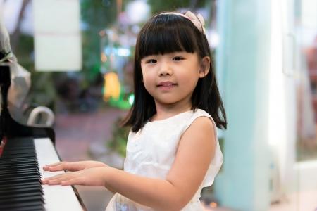 행복 한 작은 아시아 소녀는 피아노를 연주한다