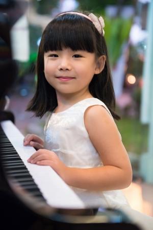 幸せな小さなアジアの女の子がピアノします。