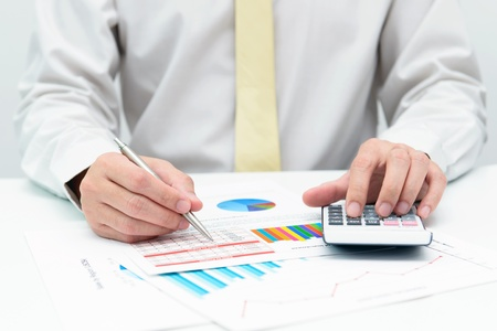 Businessman doing business financial analysis with calculator photo