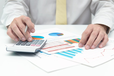 Businessman with calculator doing business data analysis photo