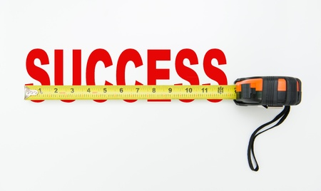 accomplishes: Tape measure over word of success isolated on white background