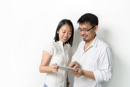 Asian man and woman viewing at tablet pc photo