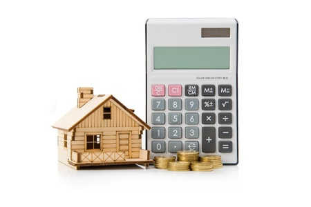 Miniature house model with calculator and gold coins photo
