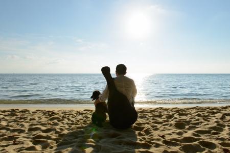 hombre solitario: Hombre solo con su perro y la guitarra en la playa Foto de archivo