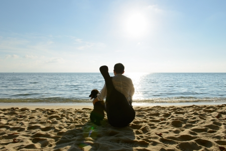 Lonely man with his dog and guitar at beach photo