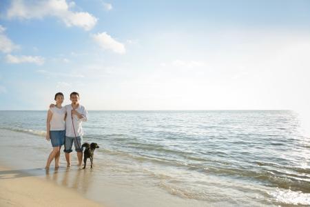 Aziatische paren met hond op het strand tegen zonlicht