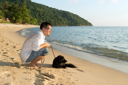Lonely man with his dog at beach photo