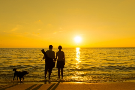 Silhouette of a couple and dog at beach during sunset photo