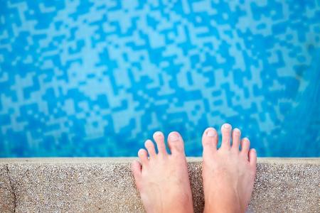 Het oog van naakte mannelijke voeten bij zwembad kant Stockfoto