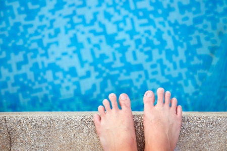 pool side: View of bare male feet at swimming pool side