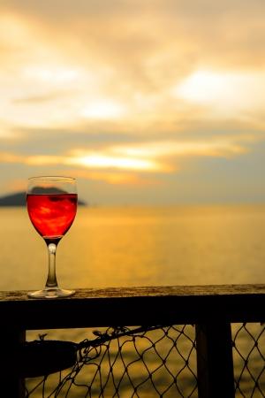 stemware: Glass of red wine against beautiful sunset