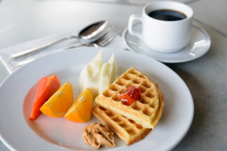 Two pieces of waffle with fruits and coffee as breakfast