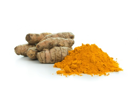 Pile of turmeric powder with fresh turmeric root