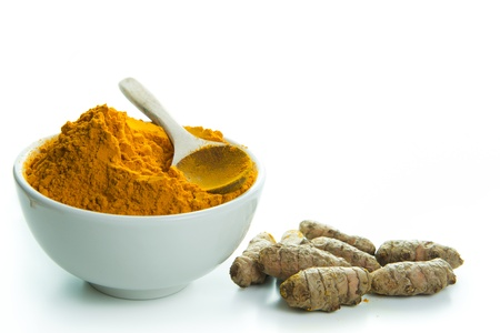 turmeric: Bowl of turmeric powder with fresh turmeric root Stock Photo