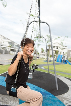 Asian elderly woman is sitting on swing happily photo
