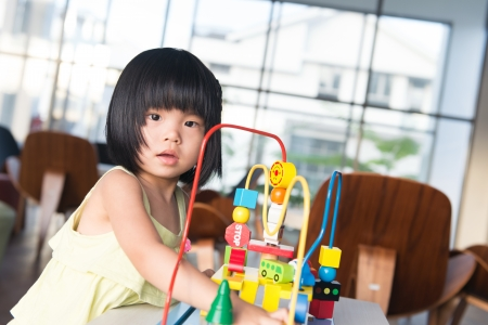 Little Asian girl playing with toy portrait photo