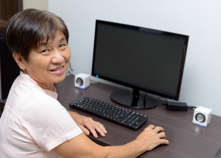 Portrait of elderly woman using desktop computer photo