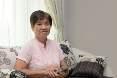 Portrait of Asian elderly lady with tablet photo