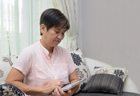 Portrait of Asian elderly lady using tablet photo