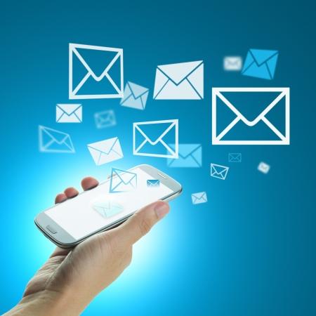 青色の背景にメールを送信するスマート フォンを持っている手
