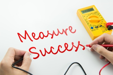 accomplishes: Measure of success conceptual using digital multimeter Stock Photo