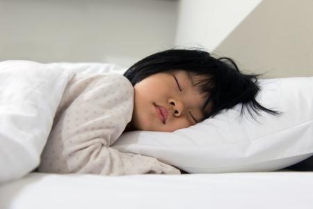enfant qui dort: Portrait d'enfant endormi asiatique sur le lit