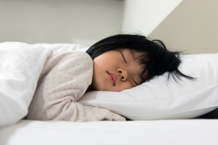 pillow sleep: Portrait of Asian child sleeping on the bed Stock Photo