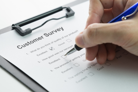 Filling in customer satisfaction survey form with pen Stock Photo - 21195371
