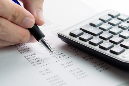 Analyzing finance report with calculator and pen Stock Photo - 21195373