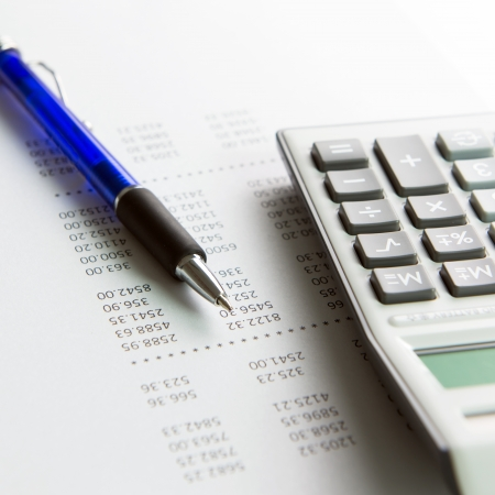 Finance analysis concept using finance report with pen and calculator photo