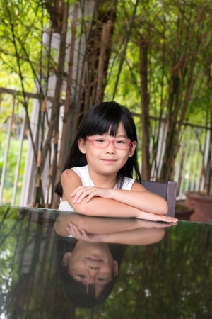 Portrait of little Asian girl with glasses