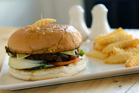 Beef burger and french fries served on white plate
