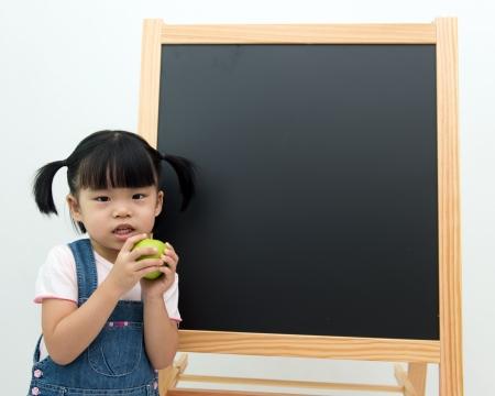 kids eating healthy: Portrait of little girl holding apple in front of the blackboard