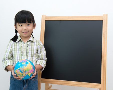 Little girl holding school globe in front of the blackboard photo