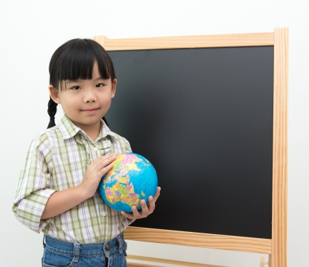 Children educational concept with girl holding globe in fornt of the blackboard