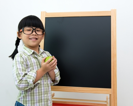 School girl wearing big spectacles posing next to a blackboard photo